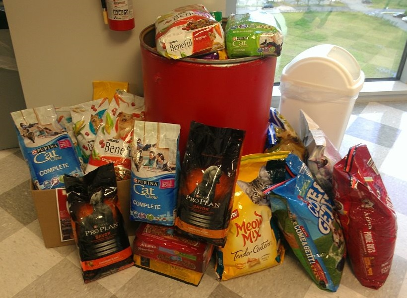 a pile and bin filled with dry dog and cat food donations for the pet food bank