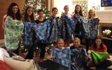a group of kids with hand made blankets that were donated