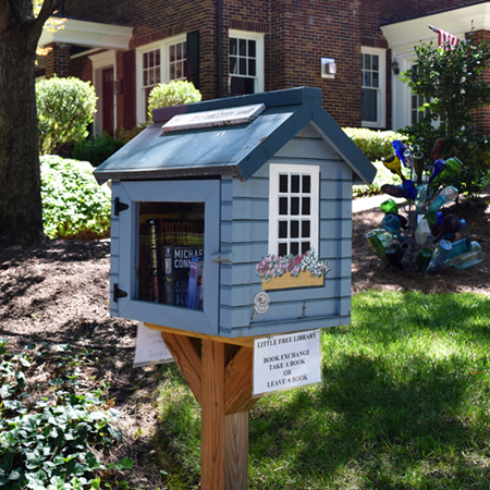 Little Free Library image in front of brick home