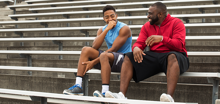 Mentor and Mentee talking on bleachers