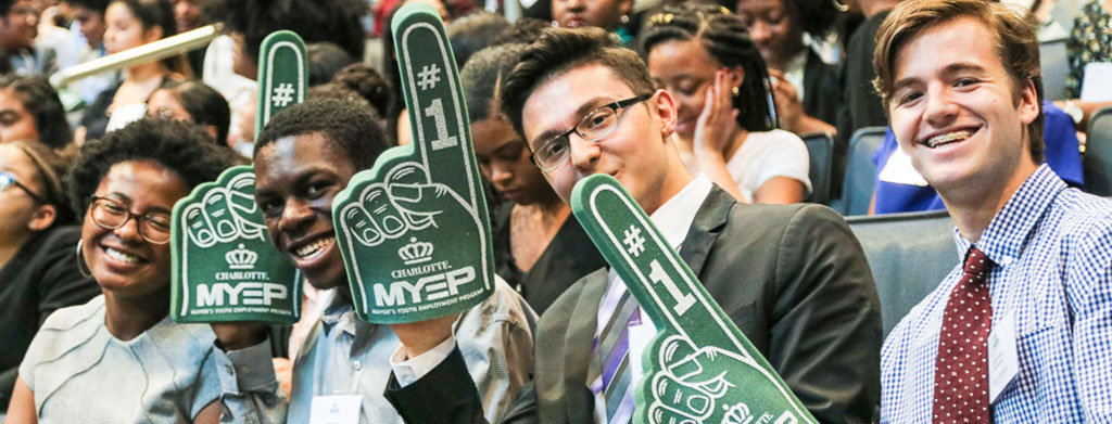 MYEP Students smiling at the camera while holding #1 hand props at the MYEP Kickoff event.