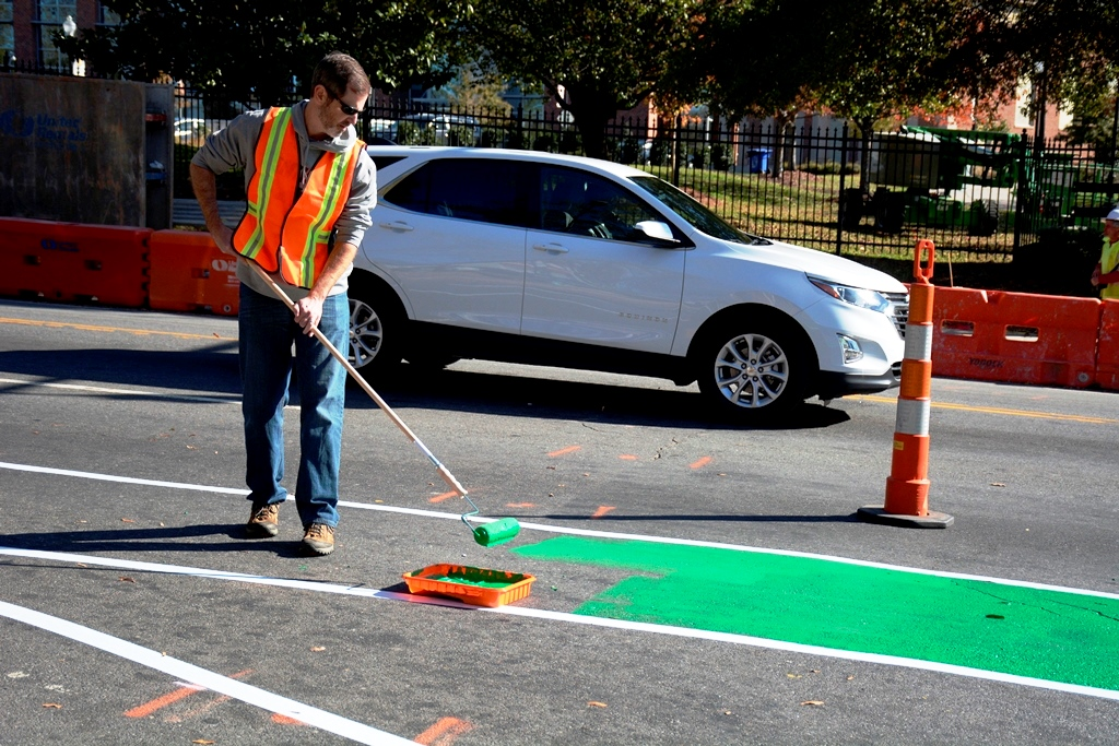Man painting bicycle lane