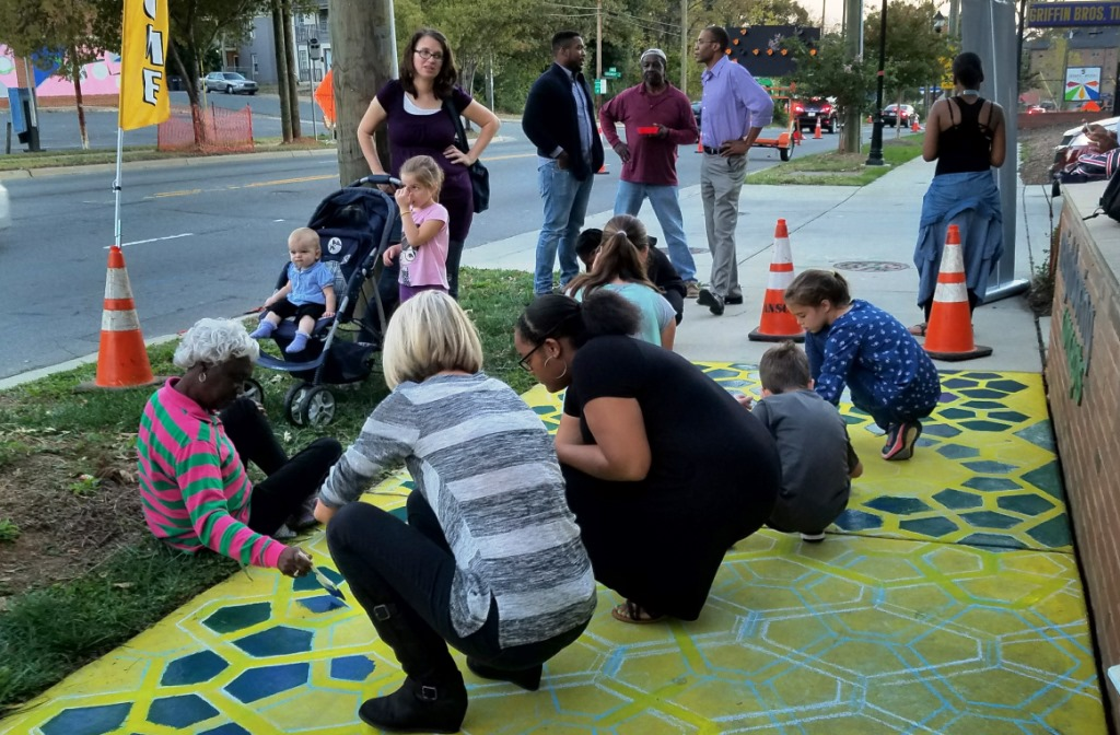 Artists and neighbors paint sidewalk in Five Points