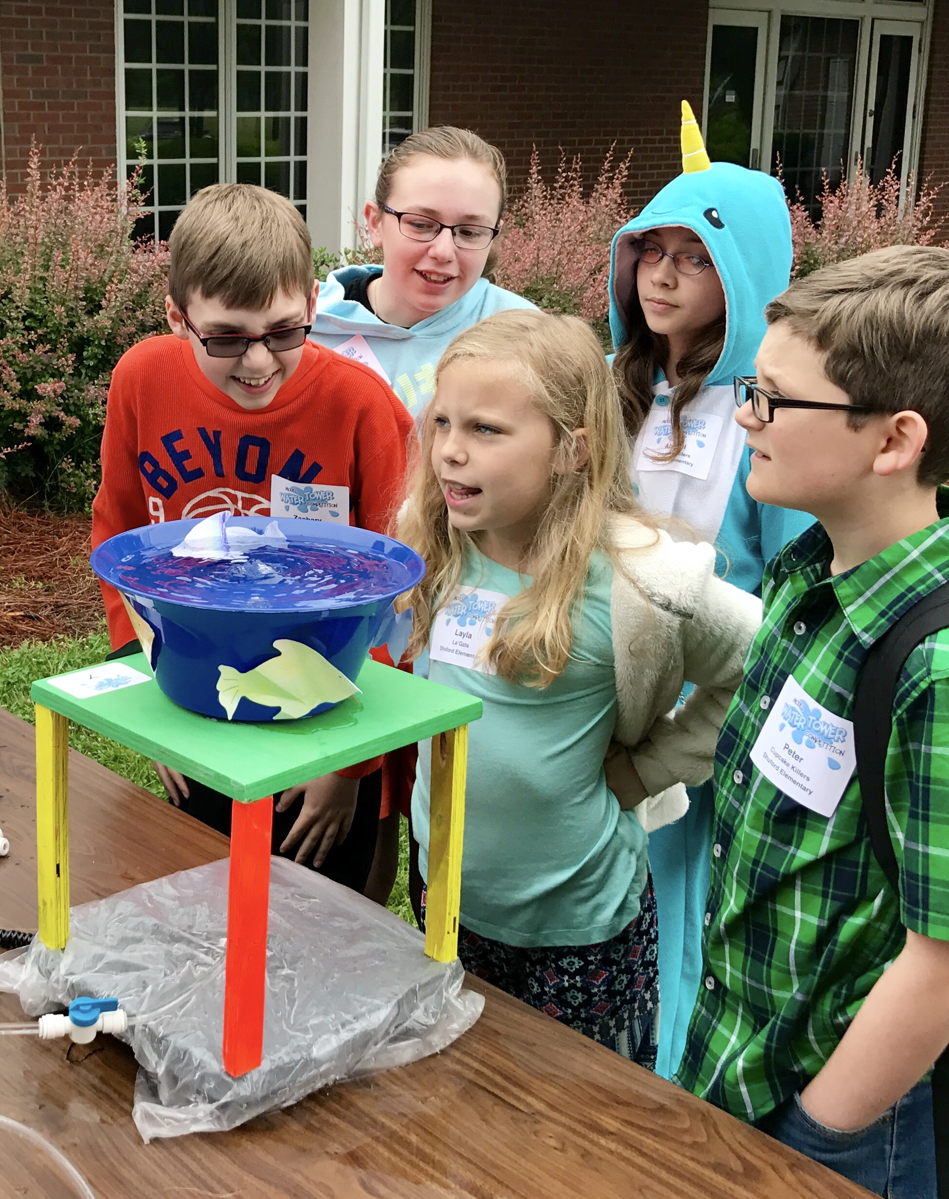 Children looking at homemade water tower design outside