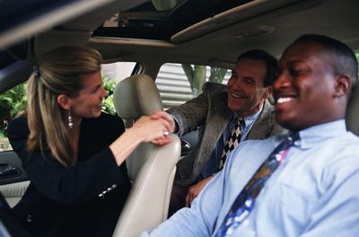 Photo of passengers shaking hands while carpooling together in a sedan