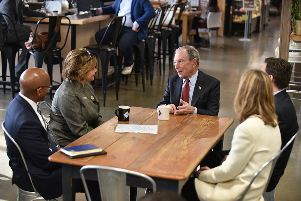 Former New York City Mayor Mike Bloomberg converses with the Charlotte team